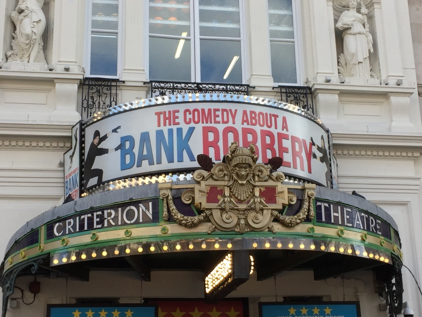 Circular canopy above the entrance to the Criterion Theatre. A small grinning face forms the centrepiece of the ornate gold crest in the middle, either side of which are the words Criterion and Theatre in white letters on a black background. Above this, on another curved panel, is the banner for Comedy About A Bank Robbery. The title of the play is in red and blue capital lettering, with a person dressed in black on each side reaching out with gloved hands to try and steal a letter from the text.