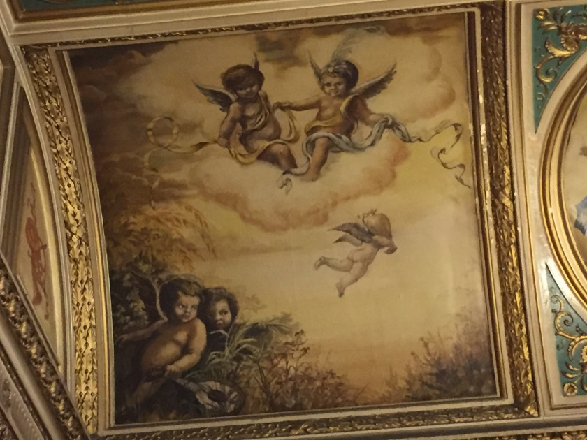 A large painting on the lobby ceiling in the Criterion Theatre. At the top, a pair of cherubs with wings sit on a large cloud together, each holding a separate length of coloured ribbon, and in each case the other end of their ribbon is floating around in the air next to them. Another cherub is flying through the air below them, and 2 more are sitting amongst the grass in the bottom left corner, one of them holding an instrument that looks like a small guitar or aukulele.