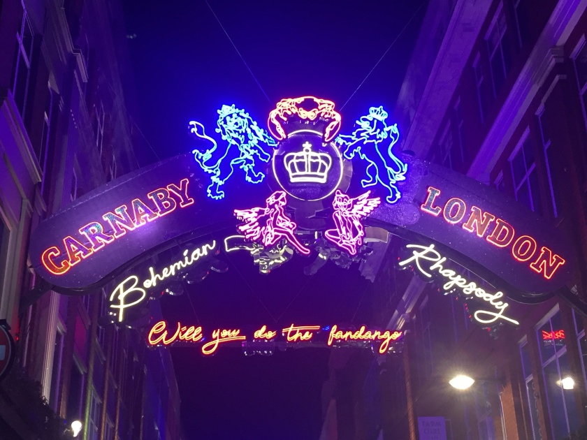 Under the night sky, a dark blue arched sign has the words Carnaby and London on each side of it in orange capitals. Just below the arch, again on each side, are the words Bohemian and Rhapsody in lit-up neon yellow curly script lettering. In the centre of the arch is the Queen crest lit up in various colours. An orange crab sits on a yellow letter Q with a yellow crown in the middle of it. 2 blue lions, one on each side, are holding up the letter Q with their front legs while standing on their back legs. 2 pink fairies are seated either side of the Q at the bottom. In the background another sign in curly orange letters says Will you do the fandango?