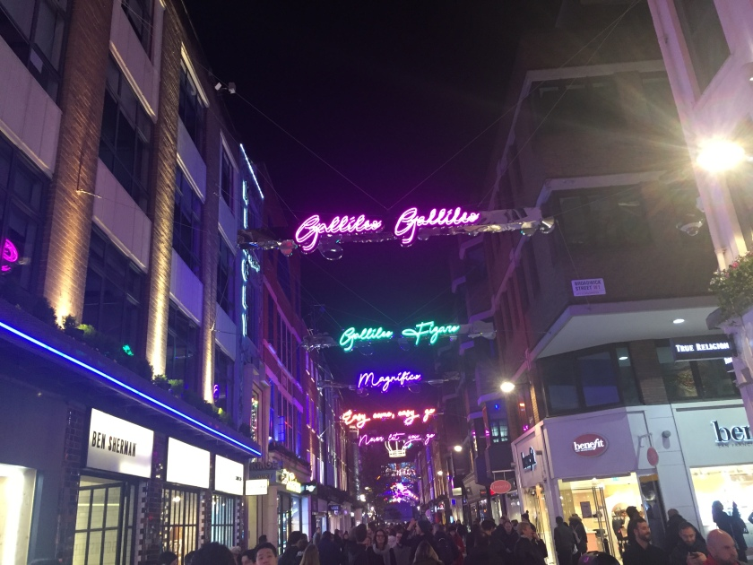 Under the night sky, various lit-up neon signs stretch across Carnaby shopping street, each with a different lyric from Bohemian rhapsody in curly script lettering. Lyrics include Galileo Galileo in pink, Galileo Figaro in green, Magnifico in blue, Easy come easy go in orange, and Never let you go in pink letters.