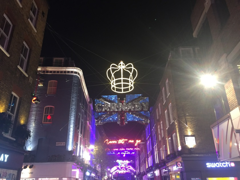 Under the night sky, a hollow outline of a crown with curving sides instead of spikes glows from the neon yellow lights it's made from. It hangs over a Union Jack sign with the word Carnaby across it in big white letters. The entire Union jack sign and lettering is made up of many glowing red, blue and white lights.