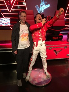 Glen smiling and wearing a white t-shirt featuring the colourful crest for the band Queen, as he stands next to a waxwork of Freddie Mercury. Freddie has a red jacket and white trousers on, and is punching the air with his left hand as he sings loudly into the microphone held in his right hand.