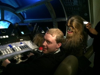 Glen sitting in the driving seat of the Millennium Falcon from Star Wars, with a waxwork of Chewbacca, a large and very hairy creature, in the seat next to him.