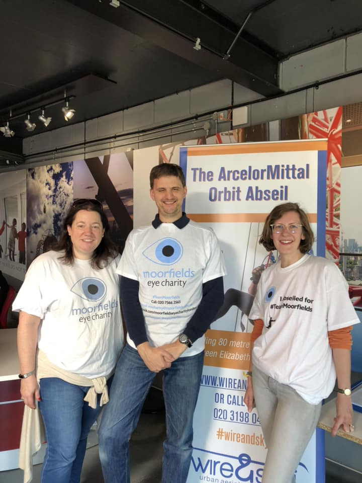 James Buller posing with another abseiler in their Moorfields Eye Charity abseil t-shirts, along with a lady from Moorfields Eye Charity, wearing a regular white t-shirt with the charity's logo on the front.