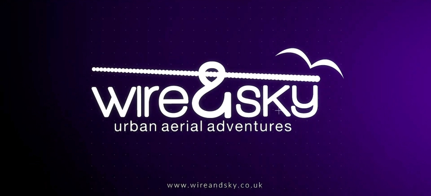 Wire & Sky logo, on a background that transitions from black to purple from left to right. The text Wire & Sky appears in the centre in large white letters, but the ampersand is styled to look like the hook on an abseil harness, with a line running through it and across the top of the words like an abseil rope. A simple silhouette of a bird is just above it on the right side. Just below the logo, smaller text says Urban Aerial Adventures, and further below is smaller text with the website address www.wireandsky.co.uk
