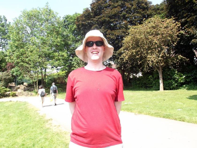 Glen smiling while standing in Lloyd Park in the sunshine, wearing a sunhat, sunglasses and a red t-shirt.