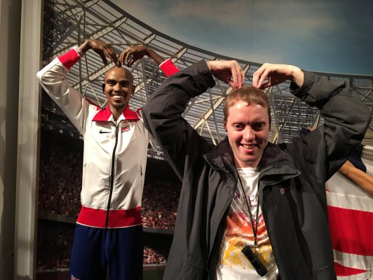 Glen next to a waxwork of Mo Farah, copying the Mobot stance that Mo is doing, placing both hands on top of his head with his fingers pointing downwards.
