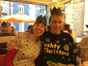 Glen with his arm around Jessica as they sit together and smile at the camera. Both are wearing Christmas hats from their Christmas crackers. Glen is wearing an Only Fools And Horses Christmas jumper, with large yellow letters saying Cushty Christmas above the yellow 3 wheeled van owned by the Trotters in the TV show, surrounded by snowflakes. Jess is wearing a white top covered in little Christmas trees, holly leaves, etc, with red sleeves.