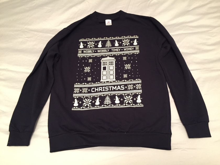 A dark navy jumper with a white design in the centre. The centre shows a large white Tardis with snowflakes falling around it. Above it are the words Wibbly Wobbly Timey Wimey, and below is the word Christmas. At the very top and bottom is a row of snowmen, snowflakes and Christmas trees.