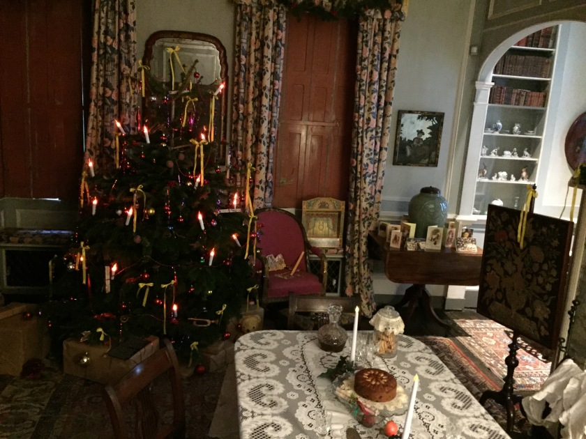 Victorian Christmas room at Fenton House, with a Christmas tree adorned with lights that look like candles, a small dining table with a couple of candles and some items of food on it, and Christmas cards on a desk.