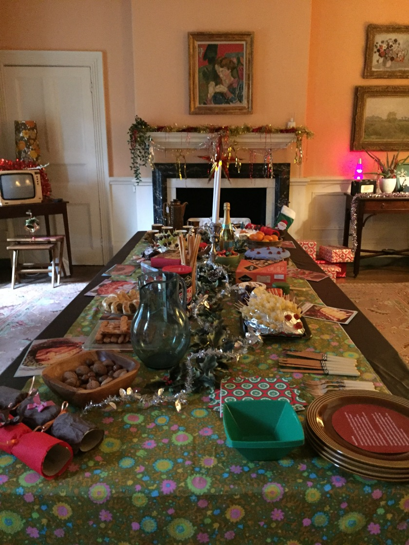 1970s Christmas dining room at Fenton House. A very long table is covered with a huge variety of cakes, snacks, fruit and other food and drink items, plus a couple of tall candles. At the far end of the room, a fireplace in the centre has tinsel across the mantlepiece, and a portrait painting above it. To the left of the fire is a small 70s television set, and to the right there is a purple lava lamp.