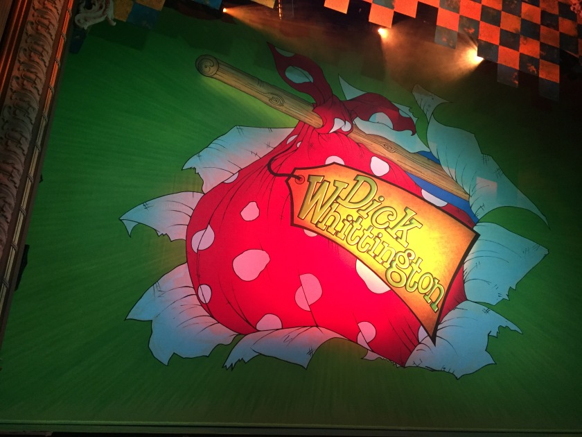 Stage curtain for the Dick Whittington pantomime, showing a large red bag with white spots strapped to the end of a wooden pole, like the one Dick carries his belongings in over his shoulder during the show. A large gold label attached to the bag says Dick Whittington in large letters.