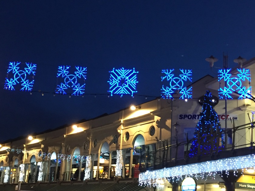 Lit-up blue snowflakes over the high street in Torquay. Behind them, a Christmas tree with blue and white lights is on a canopy above the entrance to a shopping centre. Further down the street are more arrangements of white lights in between the windows of the buildings, and other lit-up decorations suspended across the street.