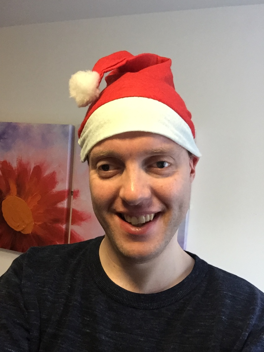 Glen smiling and wearing a red and white Santa hat.