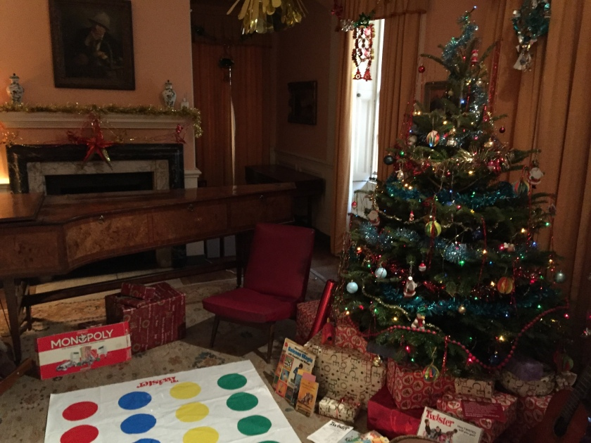In the 1970s Christmas room at Fenton House, a huge Christmas tree is covered in baubles, lights and other colourful decorations, and is surrounded by presents on the floor around it. Next to this, a game of Twister is laid out on the floor, with a Monopoly box next to it. Behind that, a large harpsichord sits in front of the fireplace, which has tinsel stretched across the mantlepiece and a large star hanging down in the centre.