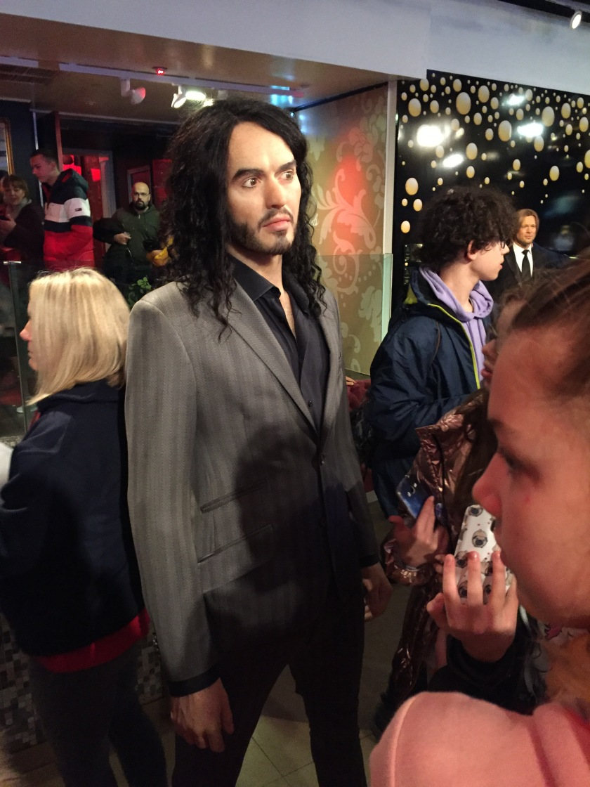 Madame Tussauds waxwork of Russell Brand wearing a grey suit.with a black shirt underneath.