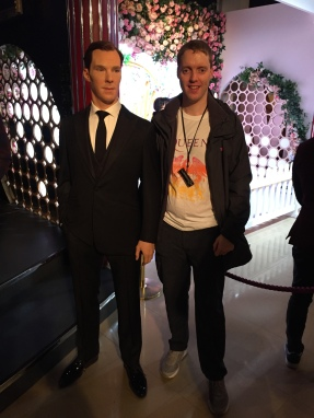 Glen posing with a waxwork of Benedict Cumberbatch at Madame Tussauds. Benedict is dressed in a smart suit, with a black jacket and trousers, long black tie and a white shirt.