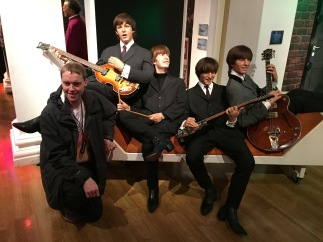 Glen kneeling and smiling towards the camera next to a long couch on which are waxworks of The Beatles. Ringo Starr is holding his drumsticks, while the other 3 are playing their guitars.
