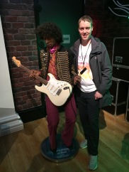 Glen posing with a waxwork of Jimi Hendrix at Madame Tussauds. Hendrix is looking down at the white and cream coloured guitar in his hands as if about to play.