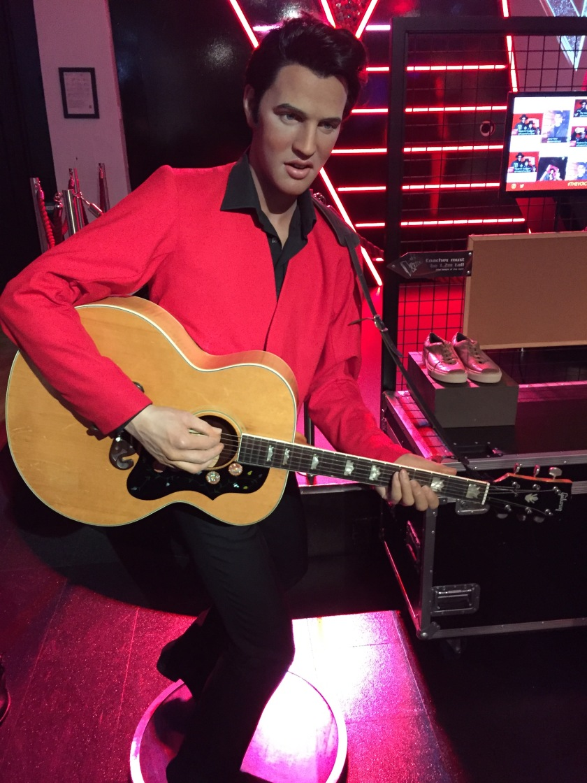 Waxwork of Elvis Presley at Madame Tussauds. He's wearing a red jacket with a black collar, and black trousers, while playing the guitar.
