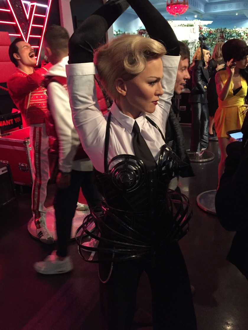 Waxwork of Madonna at Madame Tussauds. She has her arms stretched above her head. The top part of her outfit has a white shirt and a black tie, but from her breasts downwards the outfit is black. Round plastic objects sit over her breasts on the outside of her outfit, and more round objects fan out from her hips on either side.