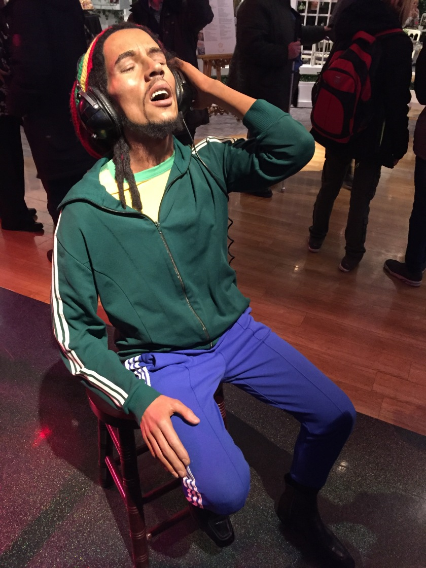 Waxwork of Bob Marley at Madame Tussauds. He is sitting with his eyes closed as he enjoys the music on his headphones, while wearing a green jacket with white stripes along the side of the sleeves, and blue trousers with shite stripes down the side of the legs.