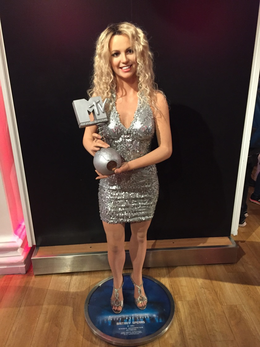 Waxwork of Britney Spears at Madame Tussauds. She is smiling and wearing a short, glittery, armless silver dress, and smiling. She proudly holds up an MTV award. It has a small round silver globe with the continents embossed on it, and a spring from the top of the globe connects it to a silver version of the MTV logo.