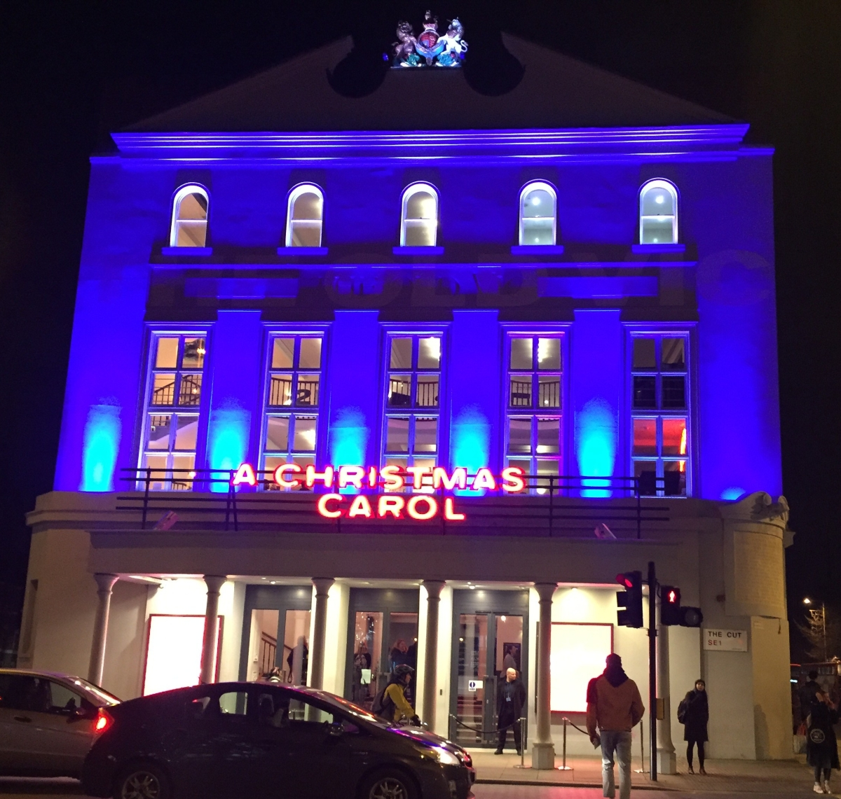 The Old Vic theatre building, all lit up in a deep blue colour, with red letters above the entrance saying A Christmas Carol.