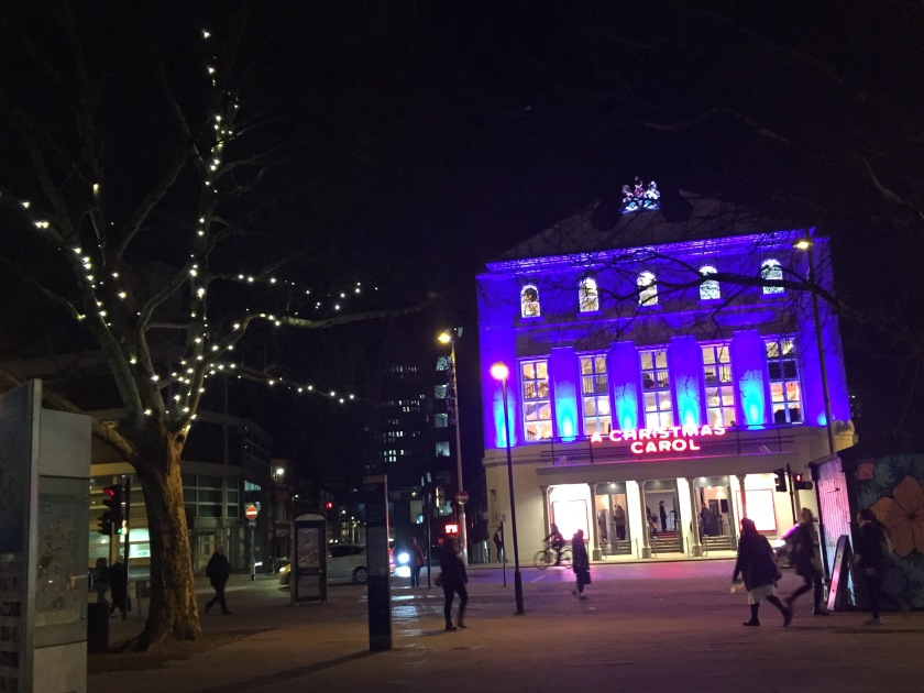 A tree with thick branches covered in lights stands across the road from The Old Vic theatre building, which is all lit up in a deep blue colour, with red letters above the entrance saying A Christmas Carol.