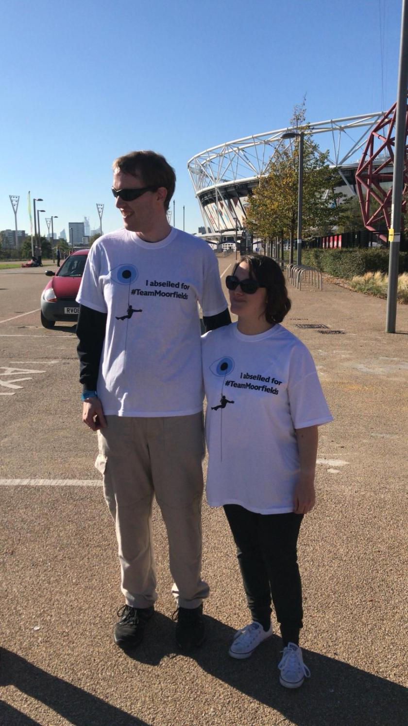 Glen and Claire standing together in the sunshine together, wearing white Moorfields Eye Charity abseil t-shirts and sunglasses, with the Olympic Stadium in the background.