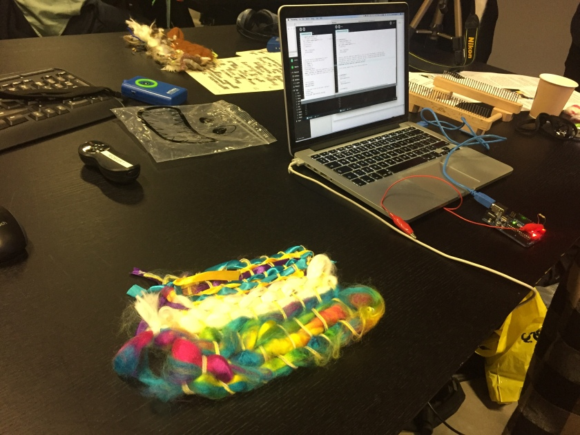 Our colourful woven creation, made of blue and yellow ribbons, white wool and rainbow coloured wool, on the desk next to a laptop, into which is plugged a small device like a Raspberry Pi, to be connected to our craftwork.