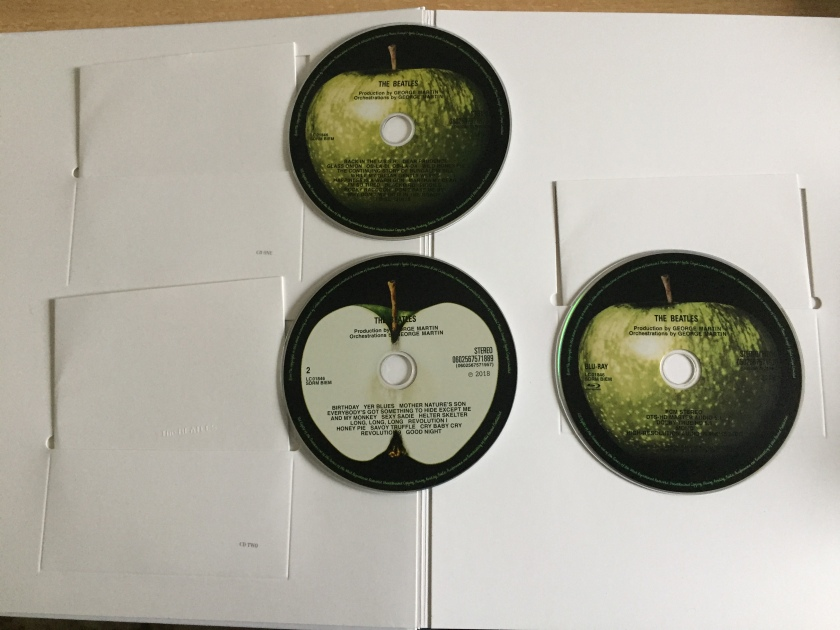 The inside front cover of the large book for The White Album boxset, showing the first 2 CDs and Blu-ray disc, and the white sleeves they came out of. The discs are each filled with a large image of an apple, which is whole on CD 1 and the Blu-ray, and cut in half on CD2 to reveal the white centre. The track listing on each disc is on top in black text.