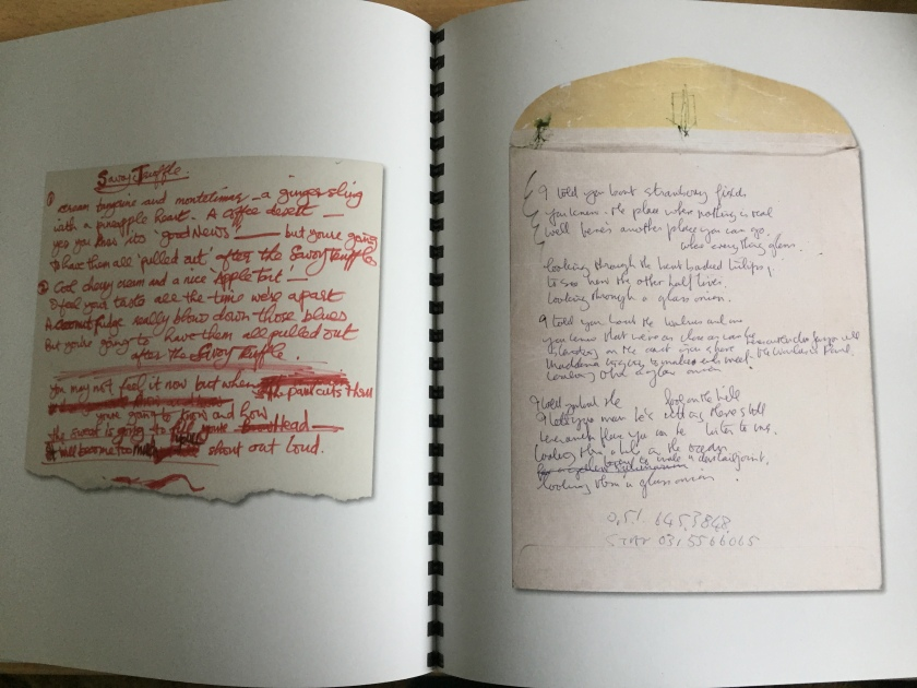 2 pages from the book for the White Album box set, each showing a colour photograph of a piece of paper with handwritten lyrics on it. The central spine between the pages is printed all the way down with small black blocks so that it looks like a binder.