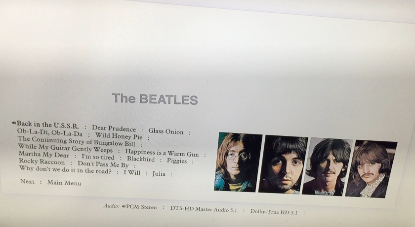 Album tracks menu on the Blu-ray disc for the White Album box set. On a white background, the tracks for the first half of the album are in black on the left, while on the right are 4 portrait photos of the band members. Audio options for stereo and 5.1 sound are at the bottom of the screen, and just above the track listing is larger grey text saying The Beatles.