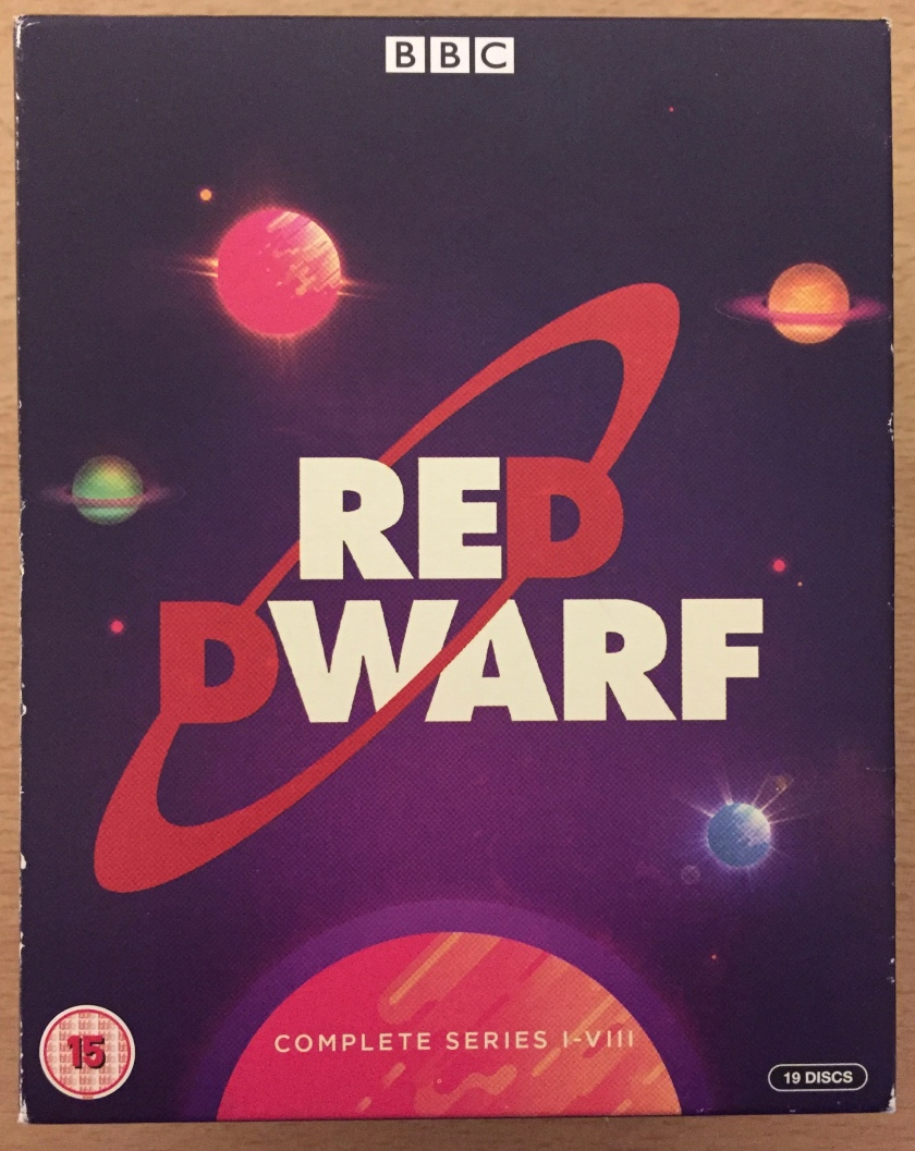 Cover of the Red Dwarf Series 1 to 8 Blu-ray box set. The logo consists of large capital letters saying Red Dwarf, one line above the other. All letters are white, except for the letter D on each line, which is red. Those 2 letters are connected by a red ring at a diagonal angle, passing behind the word Red and in front of the word Dwarf. This is all against a dark blue-ish purple background showing various coloured planets in space.