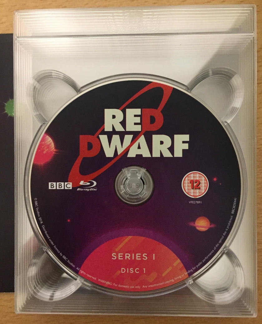 Series 1 Disc 1 in the Red Dwarf series 1 to 8 Blu-ray box set. The disc features the Red Dwarf logo against a blueish-purple background with planets floating around. The white text Series 1 Disc 1 sits over the top of an orange planet or sun sticking up from the bottom.