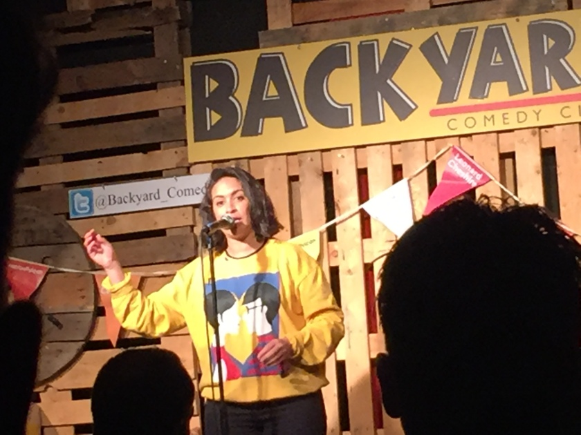 Emily Lloyd-Saini on stage at the Backyard Comedy Club. She is wearing a yellow jumper, on the front of which is artwork of a man and woman looking at each other. both with dark hair and the man wearing glasses.
