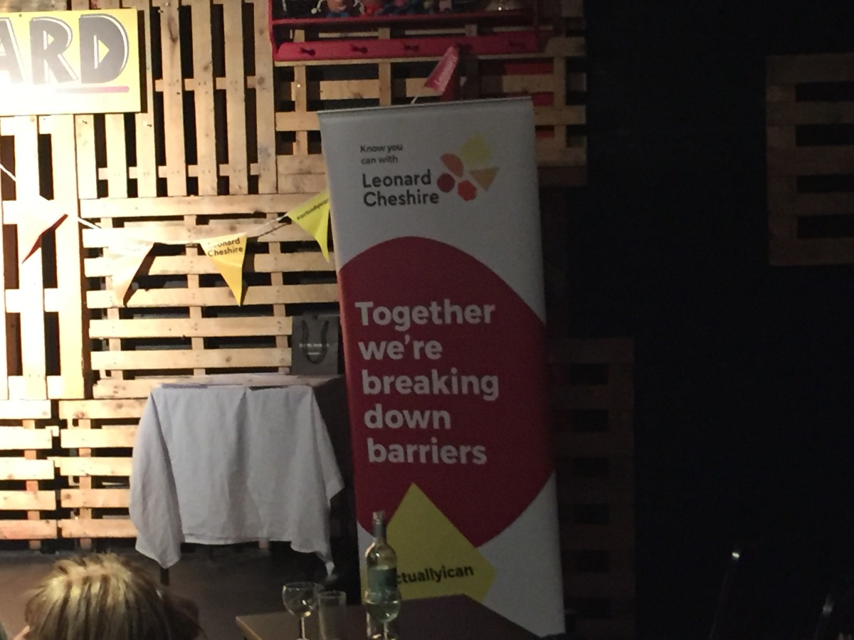 A tall banner for the Leonard Cheshire charity, on the stage at the Backyard Comedy Club. Big white text in a large dark red circle says Together we're breaking down barriers. At the bottom, black text in a small yellow triangle shows the hashtag I Actually Can.