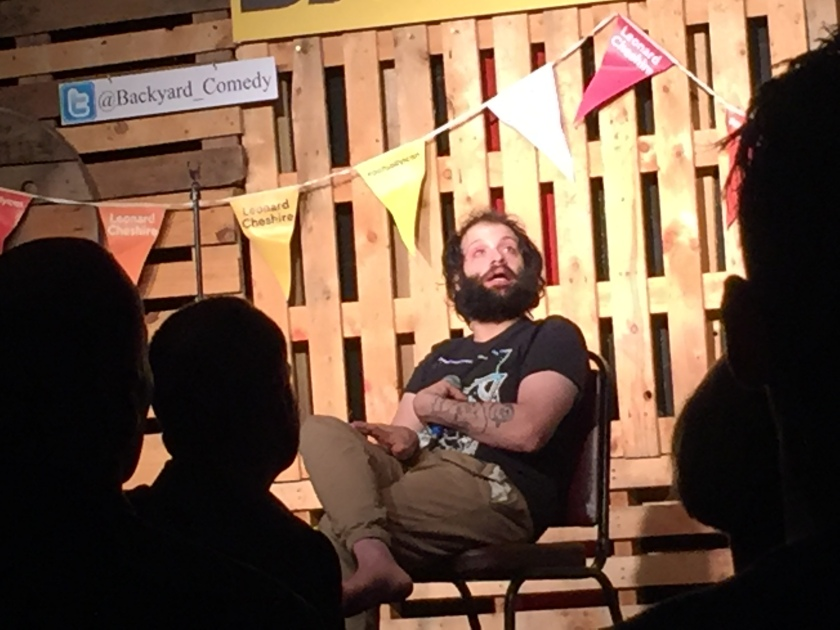 Tim Renkow, sitting on a chair on the Backyard Comedy Club stage as performs his set. He is wearing a black t-shirt, the white pattern of which is obscured by his left arm across his chest, which has a tattoo covering his forearm.