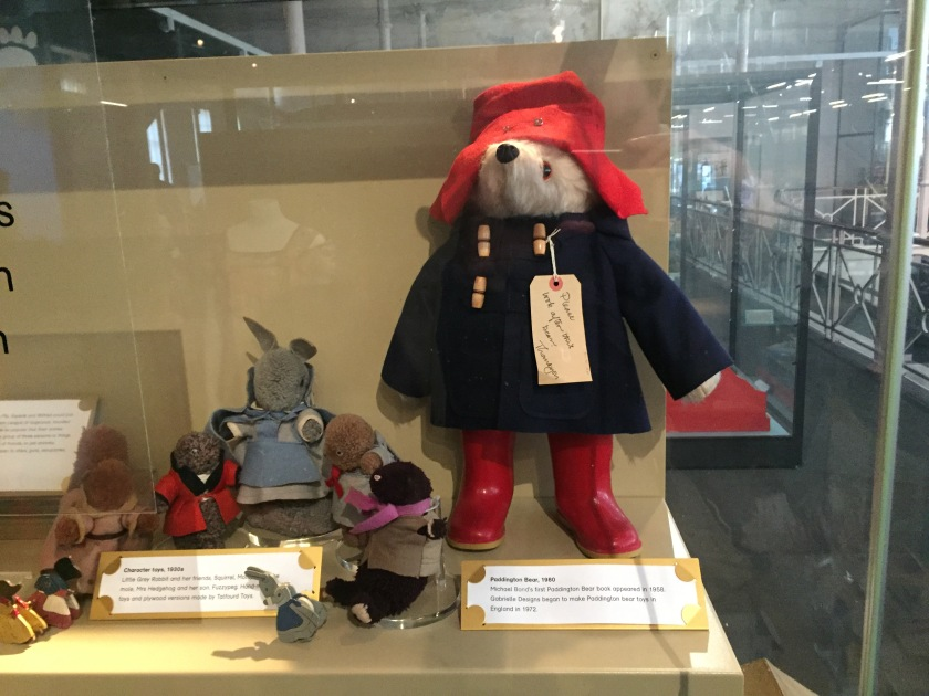 A large stuffed Paddington Bear toy, wearing a red hat, navy coat and red wellies, with a baggage label tied to one of his coat buttons that reads Please look after this bear, thank you. Next to him is a much smaller stuffed toy of Little Grey Rabbit, with her even smaller rabbit daughter and her squirrel and hedgehog friends.
