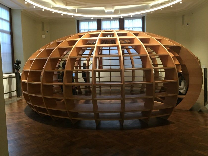 A large globe-shaped wooden structure, like a squashed ball, filling the centre of the room. The outer walls are a wooden grid all the way around, effectively creating lots of little shelves. A tall opening allows people to walk inside and sit on the circular bench round the inner edge of the structure.