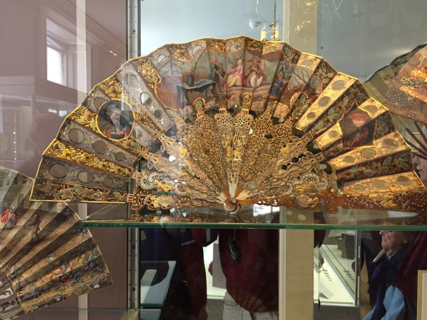 A fan spread out to reveal its ornate gold detailing, portrait paintings and artistic patterning.