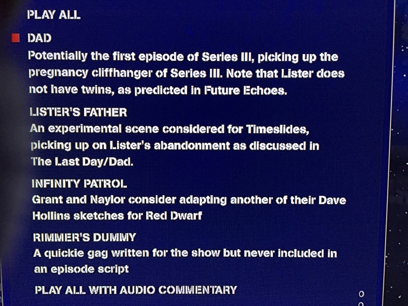 Close-up of the script extracts menu on the Red Dwarf Blu-ray box set Bodysnatcher disc, with white text on a dark blue background. Titles include Dad, Lister's Father, Infinity Patrol and Rimmer's Dummy, plus options to play them all together, with or without audio commentary.