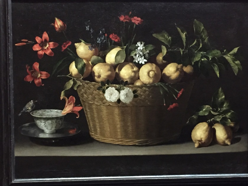 Still life painting. In the centre is a large woven basket filled with fresh lemons, along with sprigs of lemon blossom, red carnations, blue delphiniums, two white roses, day lilies and a tulip. in the bottom left is a silver bowl filled with water, on a blue-and-white porcelain bowl. A goldfinch perches on the lip of the bowl, and a day lily floats in the water.