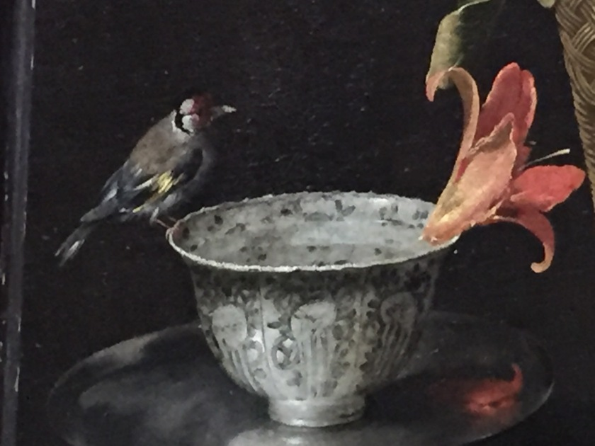 Close-up of the painting Still Life Iin A Wicket Basket, focusing on a goldfinch perched on a decorative silver bowl filled with water, opposite a day lily floating in it on the other side.