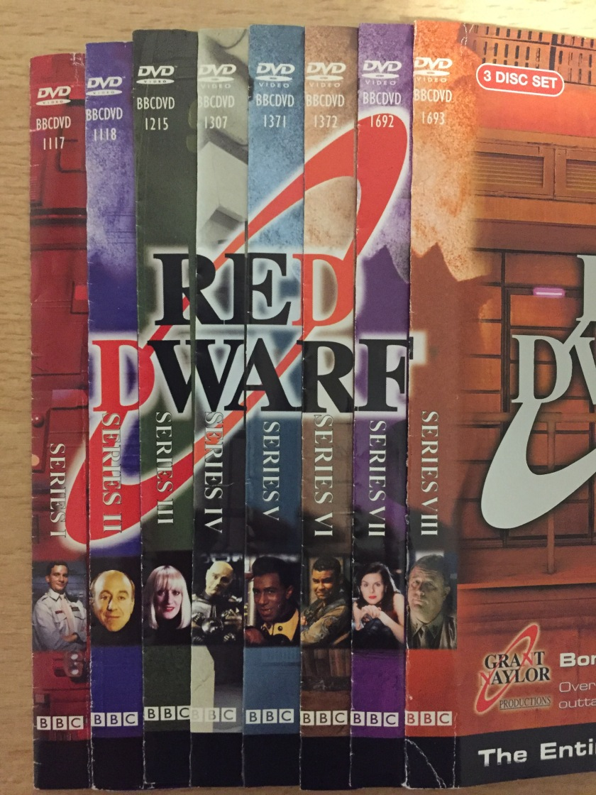 The spines of the original DVD covers for Red Dwarf series 1 to 8. Putting them together reveals the show's logo going across them.