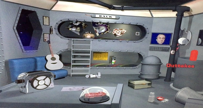 The extras DVD menu for Red Dwarf series 1. The screen shows the bunk room where Lister and Rimmer sleep, and by moving around the screen you can select various items to access different features e.g. the guitar, toaster, model of the ship, computer screen, etc.