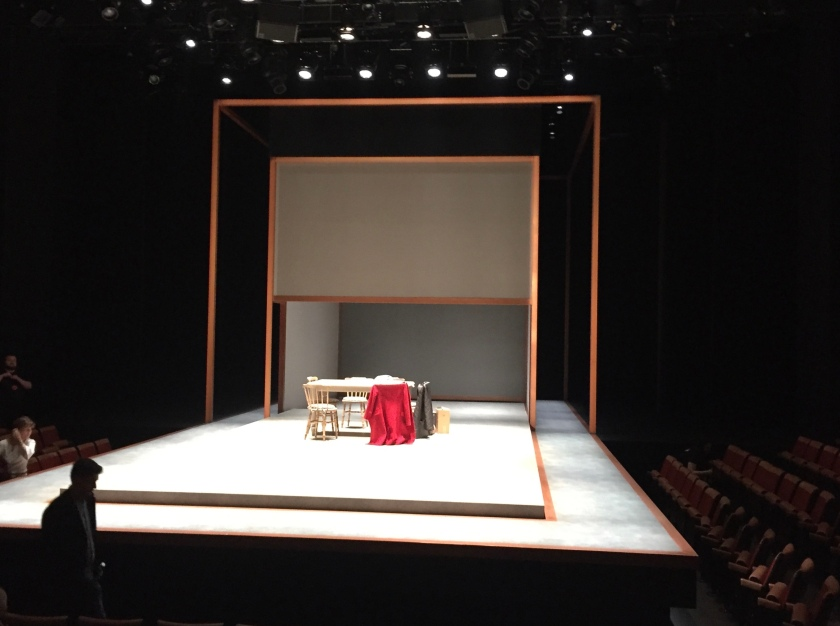 Stage for Alys, Always. A large white rectangular platform fills the stage, which stretches out into the auditorium. The platform is shallow and doesn't quite fill the stage, leaving a white walkway around the edge. A wooden table and chairs, representing a home environment, are on the stage, with a large gauze screen in the air above it.