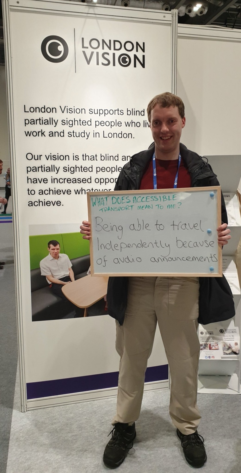 Standing in front of a tall London Vision banner, Glen is smiling and holding up a white board with handwritten text on it that says What does accessible transport mean to me? Being able to travel independently because of audio announcements.