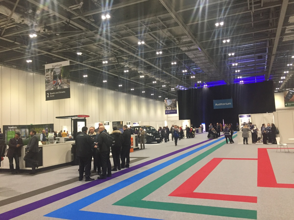 Exhibition hall for the TFL Access All Areas event, with lots of stalls divided into different zones. Large coloured lines on the grey floor can be followed to reach the coloured zones. There is also an auditorium for talks at the far end of the room.
